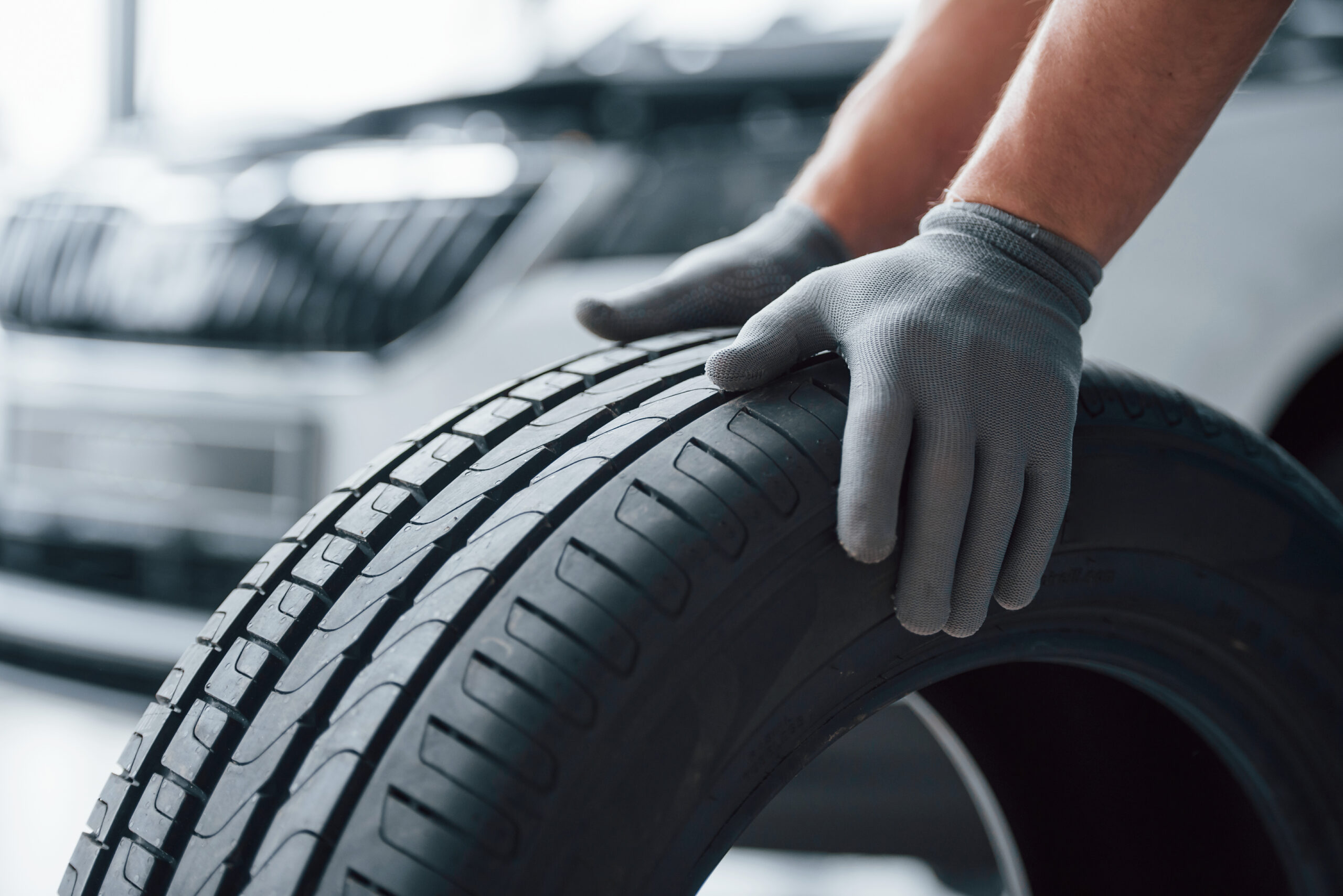Hands only. Mechanic holding a tire at the repair garage. Replacement of winter and summer tires.